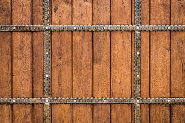Wooden gate with wrought iron elements close up