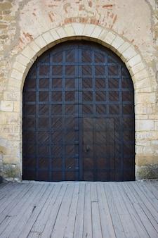 Деревянные ворота старинного средневекового замка или крепости, покрытые железными полосами. ворота имеют закрытую калитку с ручкой.