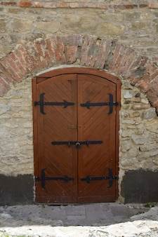 Wooden gates of an old medieval castle or fortress, covered with strips of iron. the gate has a closed wicket with a handle