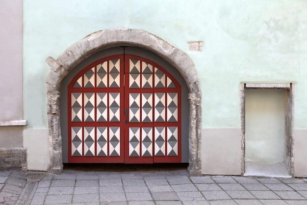 古い建物のファサードに装飾要素が付いた木製の門またはドア。タリン、エストニア。カラフルな木材のアンティークドア、石の壁、巨大な門