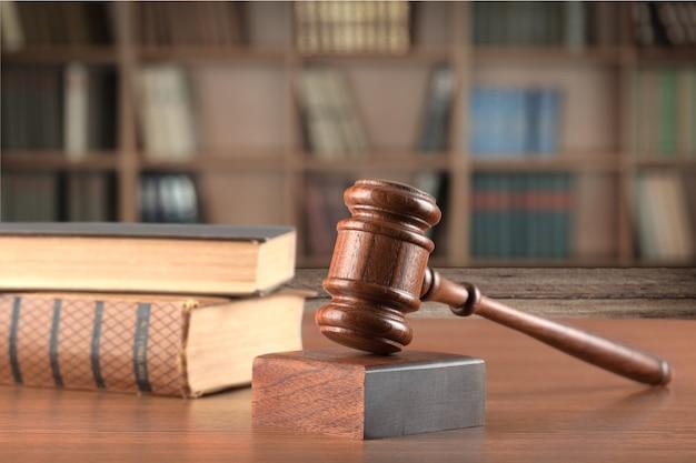Деревянный молоток и книги на фоне, концептуальная судья, зал суда и приговоры