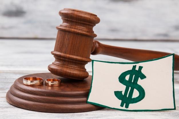 Деревянный молоток и знак доллара. обручальные кольца и знак доллара. концепция развода и распада.