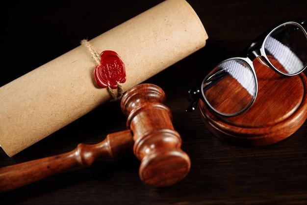 Деревянный молоток и стаканы рядом с завещанием и последней волей. нотариальные государственные инструменты крупным планом.
