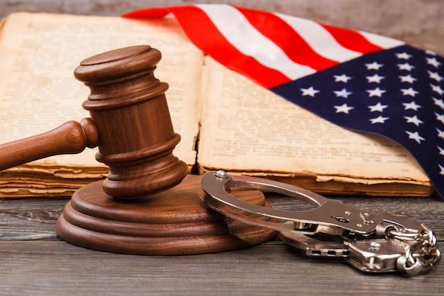 木製のガベルと手錠。アメリカの裁判所の概念における有罪判決。