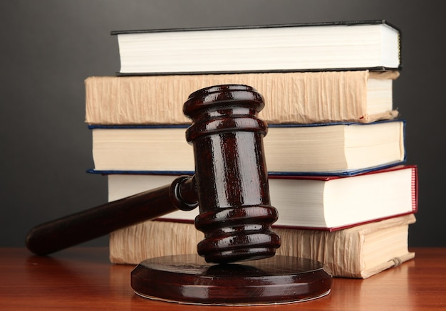 Wooden gavel and books on grey surface