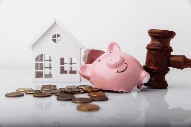 Деревянный молоток сломал копилку и модель дома с монетами крупным планом и концепцией банкротства