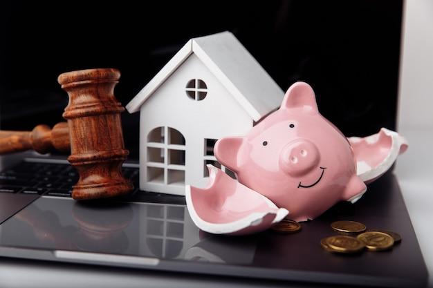 나무 망치 깨진 돼지 저금통과 집 부동산 경매 개념