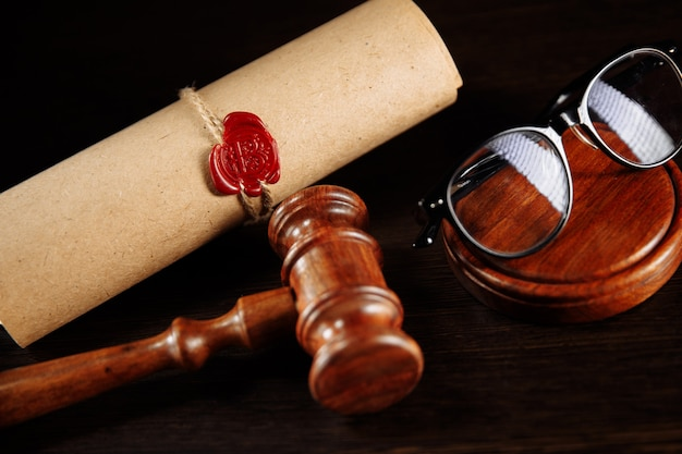 Wooden gavel and glasses near testament and last will. notary public tools close-up.