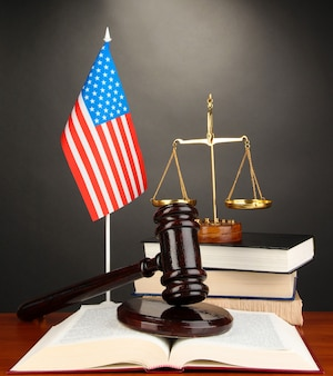 Wooden gavel, golden scales of justice  and books on grey