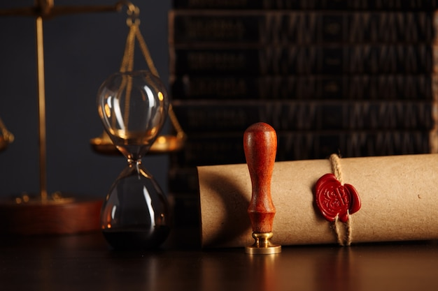 Wooden gavel, hourglass, books and stamp on testament and last will on wooden table. notary public tools.