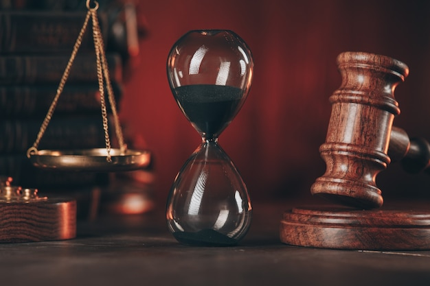 Wooden gavel, hourglass and scales on wooden table