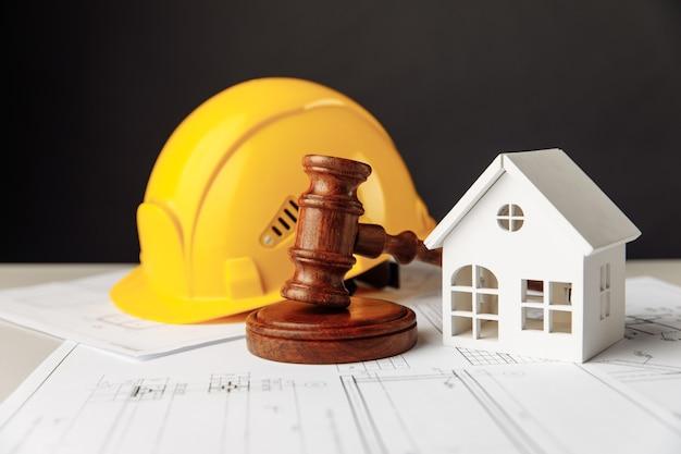 木製のガベルの家と黄色いヘルメット