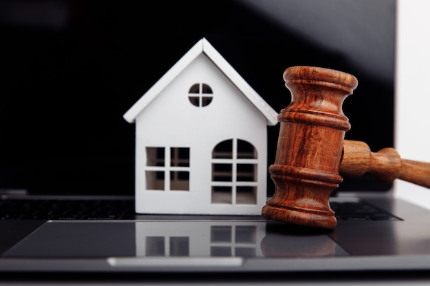 Wooden gavel and house on a laptop closeup online auction concept