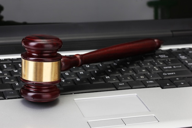 Wooden gavel on laptop computer close up