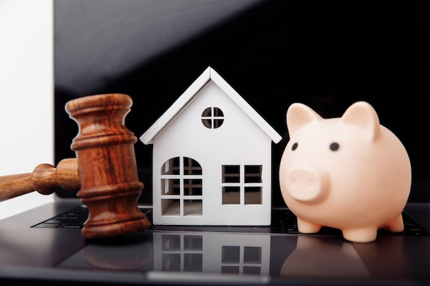 Wooden gavel piggy bank and house on a laptop online auction concept