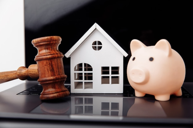 Wooden gavel piggy bank and house on a laptop online auction