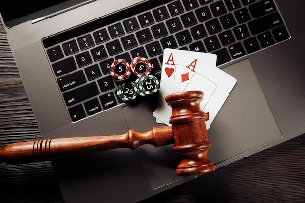 Деревянный молоток, игральные фишки и карты на клавиатуре ноутбука. понятие закона и регулирования азартных игр