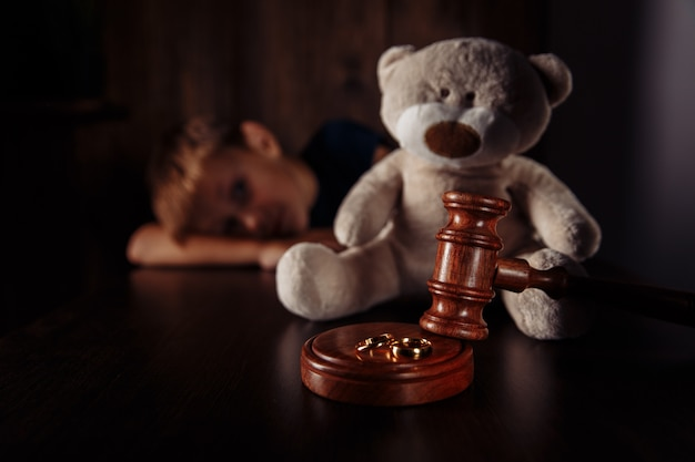 Wooden gavel rings and frustrated boy with teddy bear family law