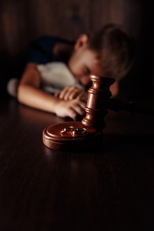 Wooden gavel rings and frustrated little boy with teddy bear family divorce effect on children