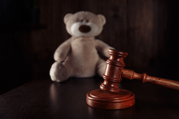 Wooden gavel and teddy bear as a symbol childrens protection