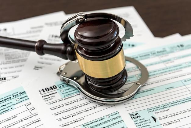 納税申告書の上に横たわっている手錠と木製のガベル。税金の時間、違法な概念
