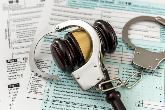 Деревянный молоток с наручниками, лежащий на налоговой декларации. время для налогов, незаконной концепции