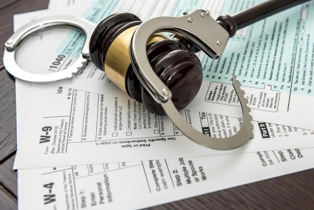納税申告書の上に横たわる手錠の付いた木の小槌