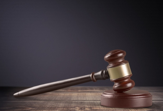 Wooden gavel on wooden table, on  background
