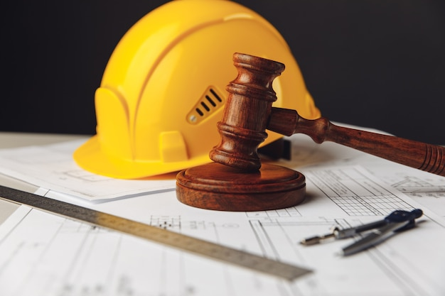 Wooden gavel and yellow helmet with drawing tools construction law concept