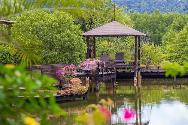 Wooden gazebo with sun loungers for relaxing on a terrace with flowers next to a lake on the tropical island of thailand. nature and travel concept
