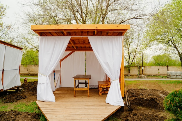 Wooden gazebo with white curtains for lunch in nature