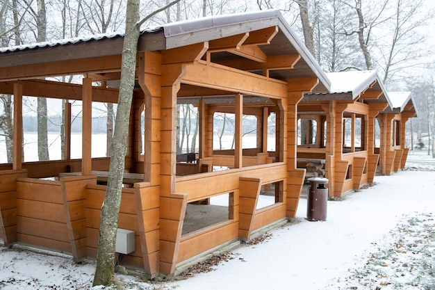 Wooden gazebos in nature in winter. cloudy weather