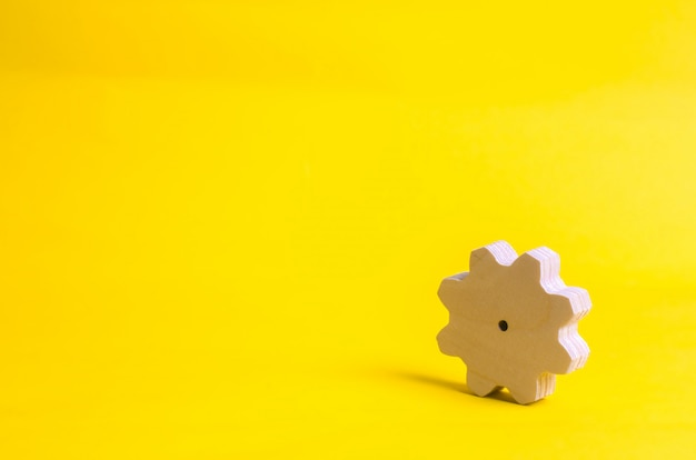 A wooden gear on a yellow background. the concept of technology and business processes.