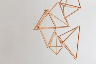 Wooden geometric decor hanging from ceiling isolated on white wall background.