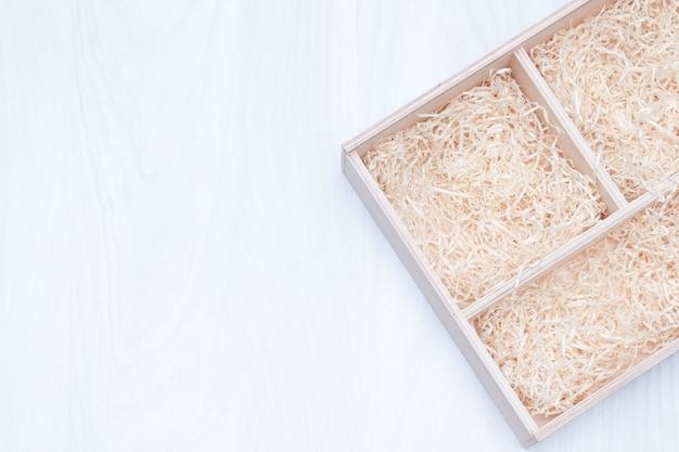 Деревянная подарочная коробка с декоративной соломкой или наполнителем.