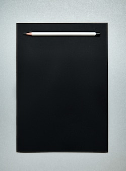 Деревянный серый карандаш на черной бумаге. офисные принадлежности. вид сверху. плоская планировка