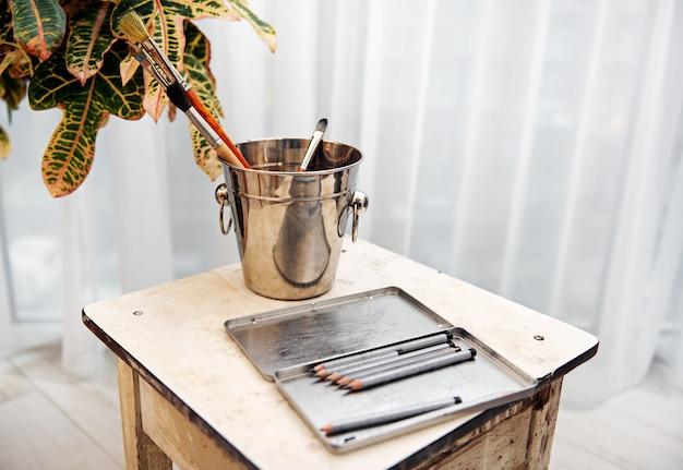 Деревянные серые карандаши в коробке, кисти в металлическом ведре на старом белом деревянном стуле