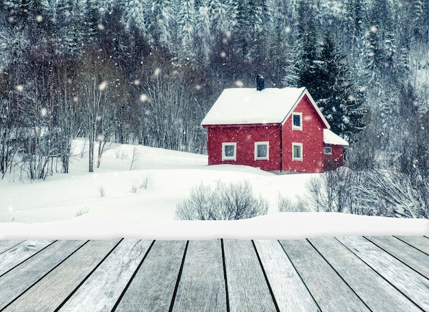 Wooden gray with red house in snowing on winter