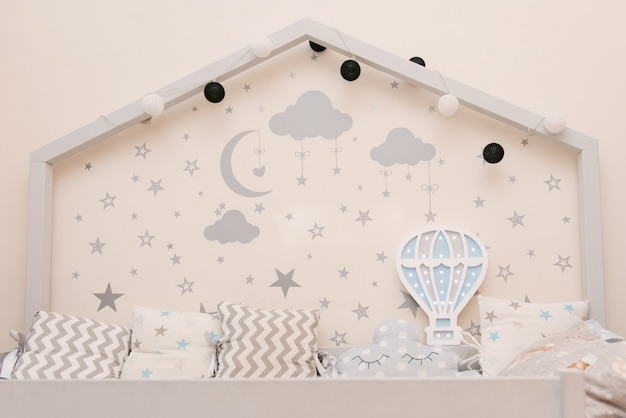 壁に星と月のある家の形をした木製の灰色の白いベビーベッド、風船、子供の部屋の装飾の形をした木製の夜の光