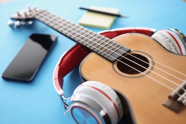 Деревянные гитарные наушники и смартфон на синем фоне