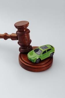Деревянный молоток судьи и игрушечный автомобиль на белом фоне. страхование, судебное дело. вертикальное изображение.