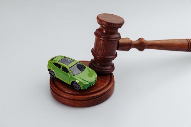 Деревянный молоток судьи и игрушечный автомобиль на белом фоне. страхование, судебное дело.
