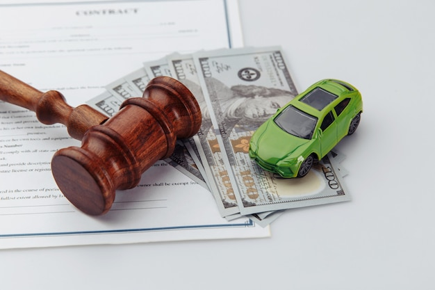 Wooden hammer, toy car, money and contract, auction concept.