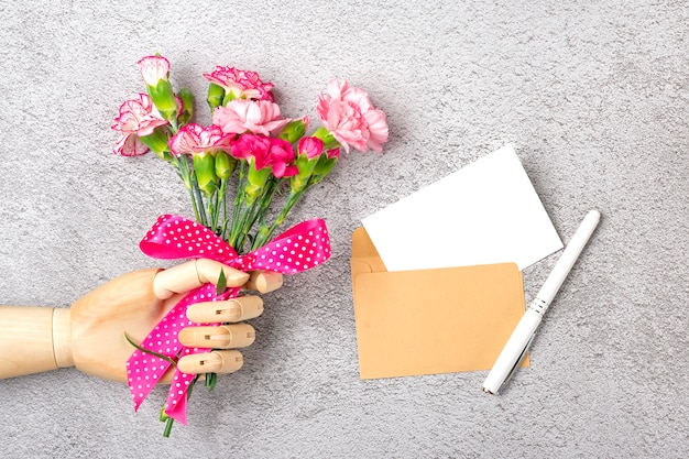 Wooden hand hold colorful bouquet of different pink carnation flowers, craft envelope, paper isolated on grey background