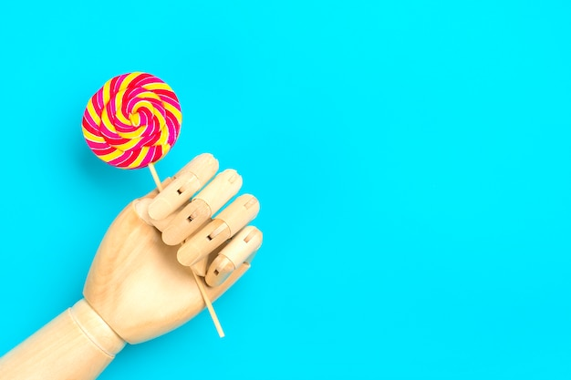 Wooden hand hold lollipop with stripes on stick on blue background flat lay top view