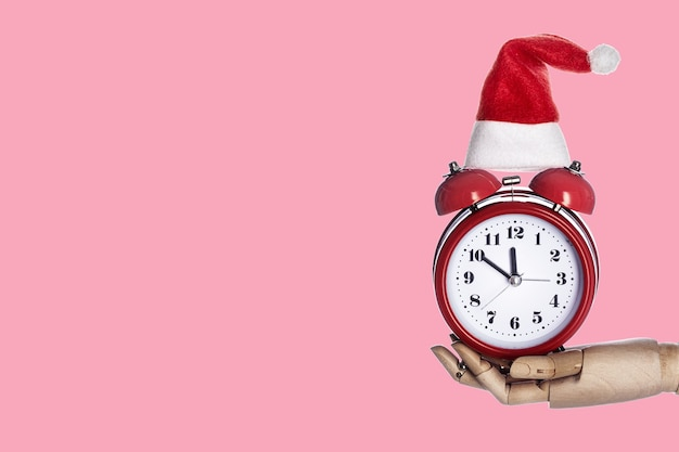분홍색 파스텔 유행의 배경에 알람 시계를 들고 있는 나무 손. 크리스마스 최소한의 모형. 인사말 카드에 대한 템플릿 모형은 텍스트 디자인입니다. 기쁜 성 탄과 새 해 복 많이 받으세요 인사말 카드
