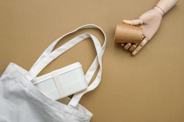 Деревянная рука, держащая коричневый бумажный стаканчик из крафт-бумаги возле хлопкового мешка с ланчбоксом на бежевом фоне. вид сверху, плоская планировка.