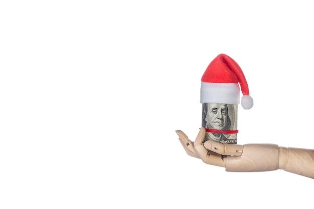 Деревянная рука, держащая рождественский денежный подарок с шляпой санта-клауса на белом фоне. минимальная концепция рождества. зимняя и новогодняя открытка. шаблон макета поздравительной открытки текстовый дизайн