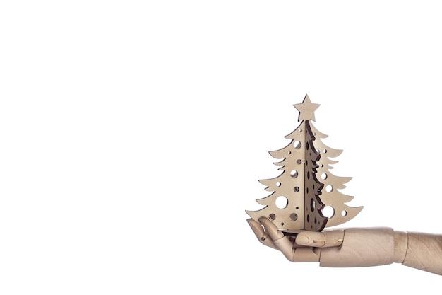 Деревянная рука, держащая елку, изолированную на белом фоне. минимальная концепция рождества. зимняя и новогодняя открытка. шаблон макета поздравительной открытки текстовый дизайн