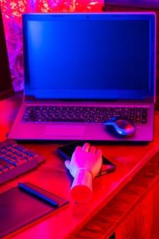 태블릿, 스마트 폰 및 핑크색과 파란색 네온 불빛이있는 키보드로 펜을 들고 나무 손